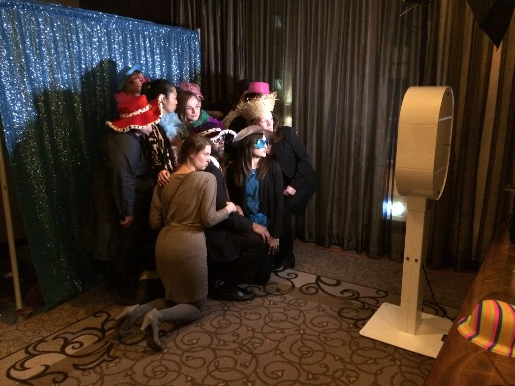 a group of friends using a digital photo booth rental at a party